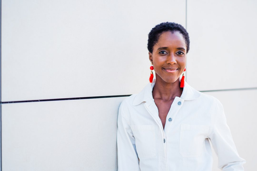 A black woman in a white shirt and red earrings smiling and leaning agains a grey wall